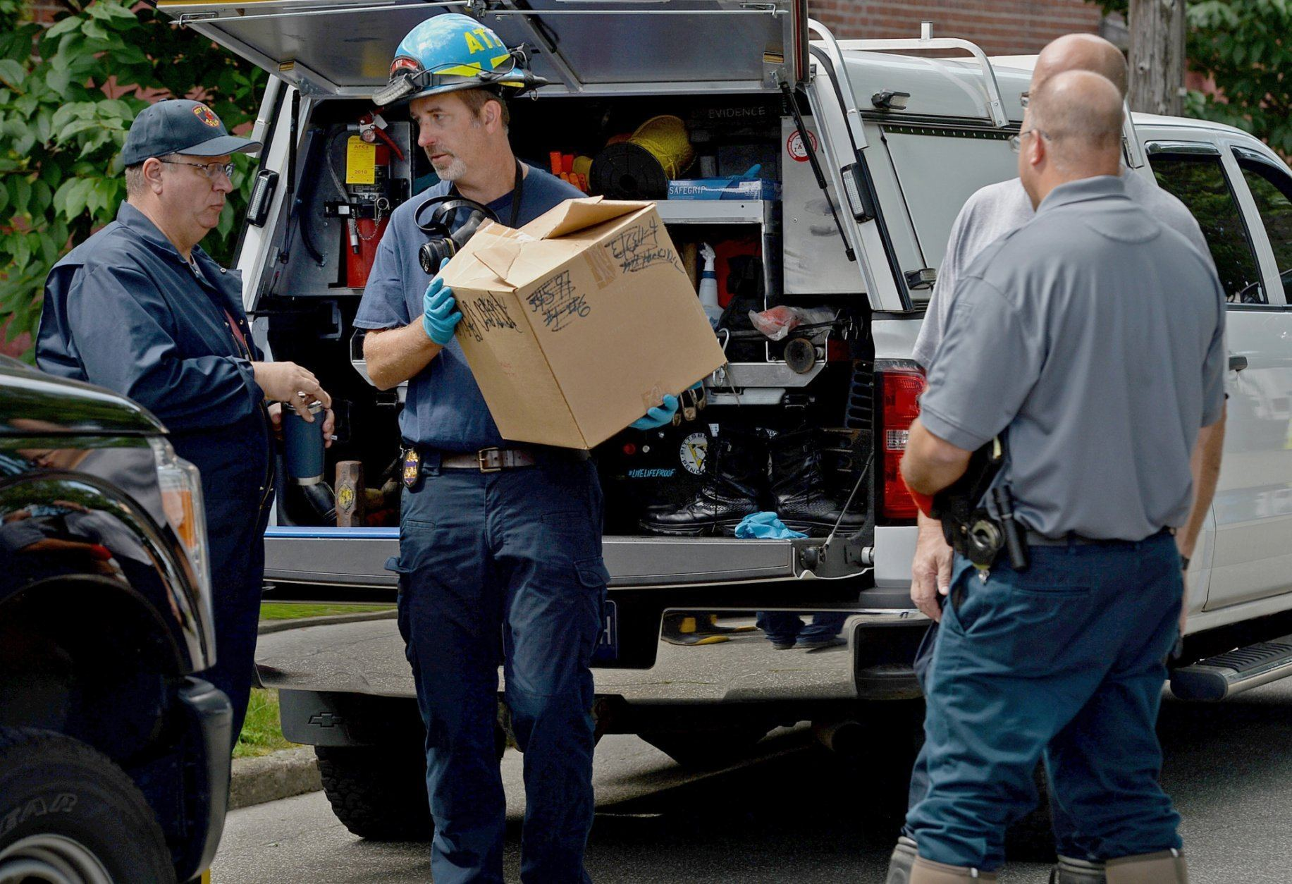 Erie Bureau of Police Det. Dave Walker, left, and Matthew Regentin, center, a fire investigator with the federal Bureau of Alcohol, Tobacco and Firearms and Explosives, based in Pittsburgh, are shown Monday, Aug. 12, 2019, with a box of evidence taken from the scene of a fatal fire at a home child care center on W. 11th Street in Erie, Pa. Investigators spent several hours at the site, where five children died and at least two others were injured in the fire the day before. (Christopher Millette/Erie Times-News via AP)