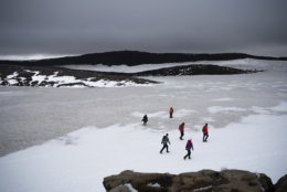 People walk on snow atop the Ok volcano crater on their way to a ceremony  by the area which once was the Okjokull glacier, in Iceland, Sunday, Aug. 18, 2019. With poetry, moments of silence and political speeches about the urgent need to fight climate change, Icelandic officials, activists and others bade goodbye to the first Icelandic glacier to disappear. (AP Photo/Felipe Dana)
