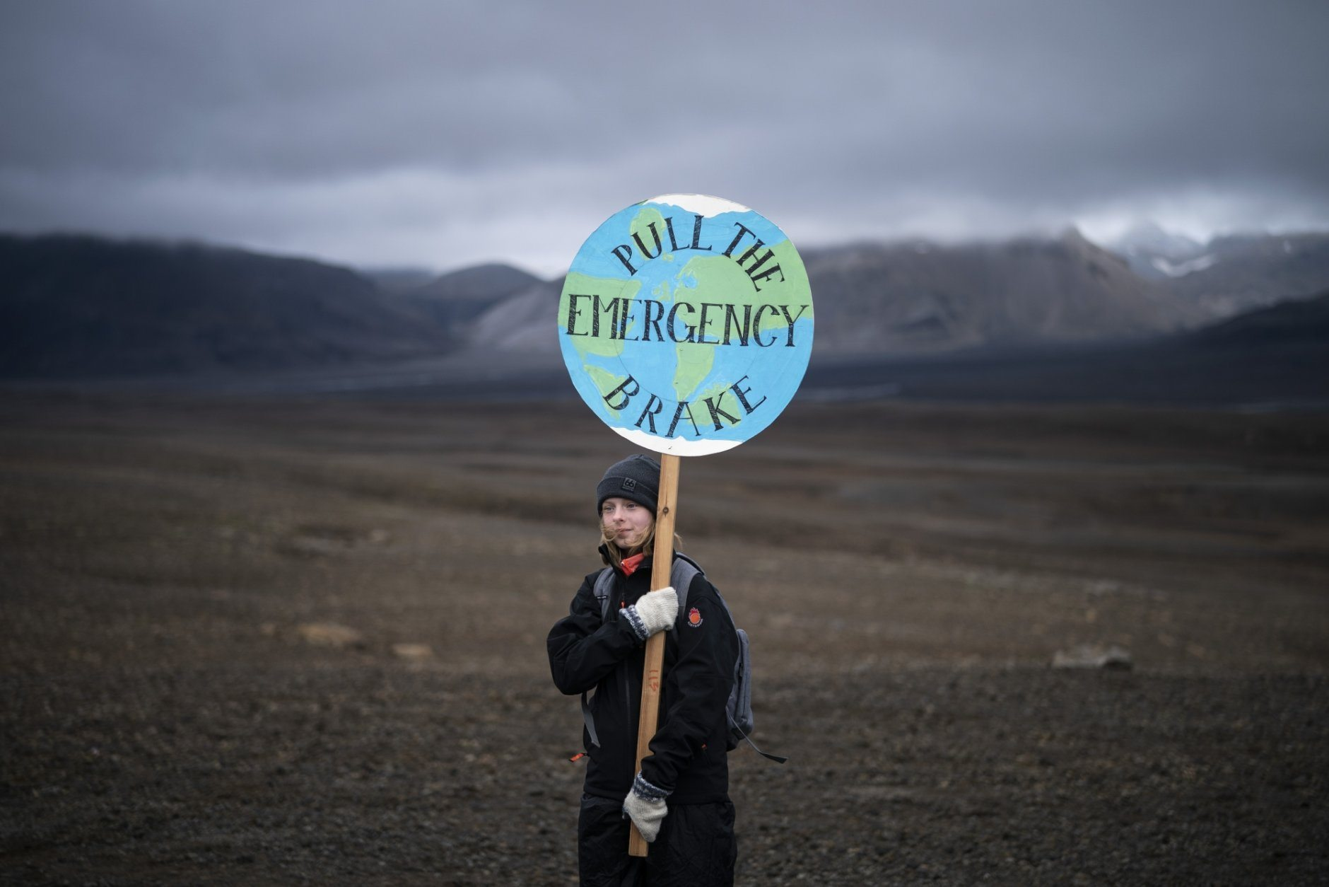 A girl holds a sign that reads 'pull the emergency brake' as she attends a ceremony in the area which once was the Okjokull glacier, in Iceland, Sunday, Aug. 18, 2019. With poetry, moments of silence and political speeches about the urgent need to fight climate change, Icelandic officials, activists and others bade goodbye to the first Icelandic glacier to disappear. (AP Photo/Felipe Dana)