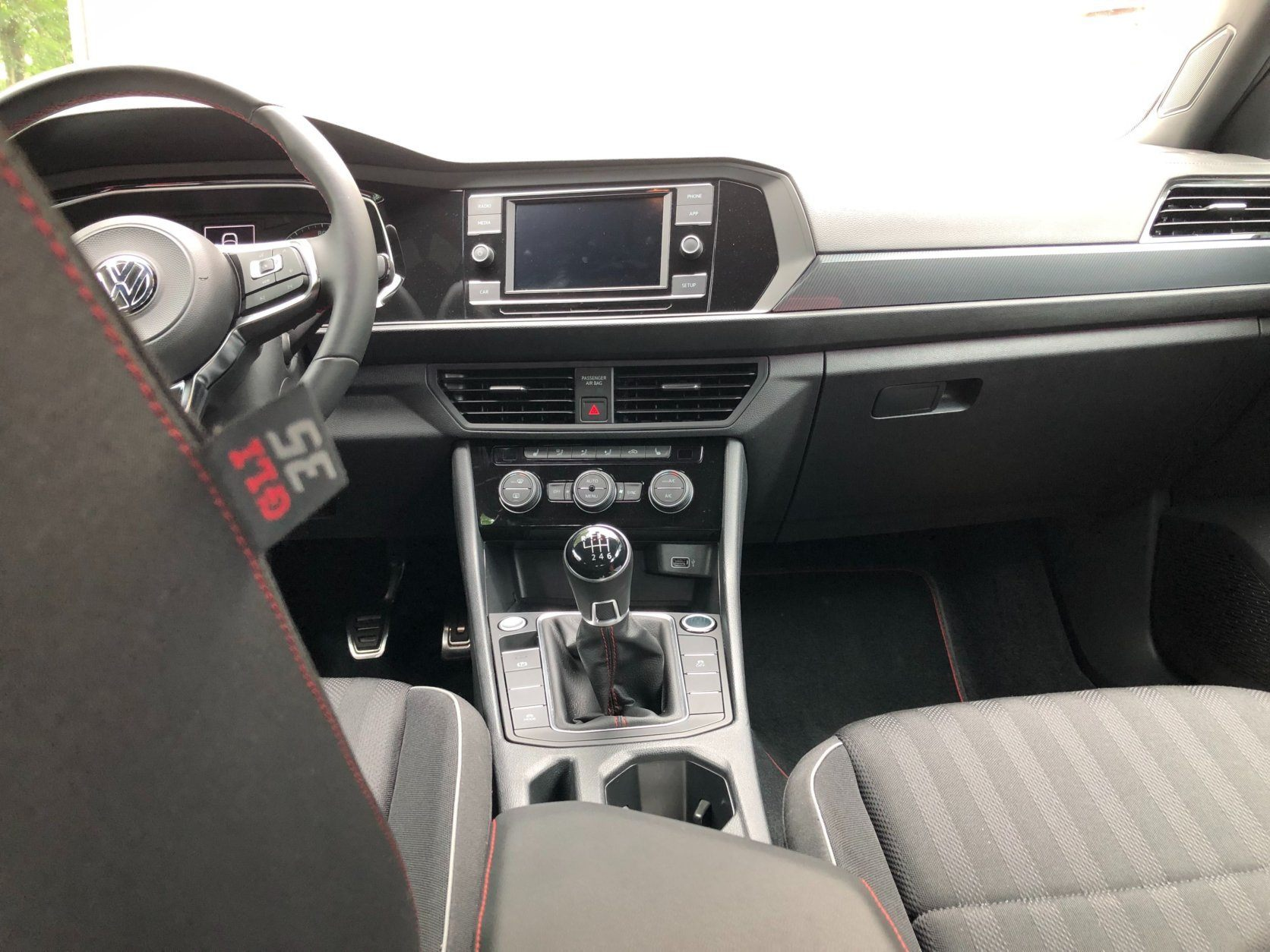 <p>Inside, the 2019 VW Jetta GLI is more German with lots of dark colors like gray and black. The materials seem like a higher caliber with the redesign this year. They have a high-quality feel when you touch them and less built-to-price.</p> <p>The GLI interior has some cool touches like the sport flat-bottom steering wheel that feels solid in your hands.</p> <p>The usual austere interior has some bright aluminum pedals and red stitching on the shifter, steering wheel and seats that make the interior pop. The cloth sport seats provide nice comfort and the heated seats work well.</p> <p>Those seats don't provide the best support when you are hitting those fast back roads; you tend to slide around a bit.</p>