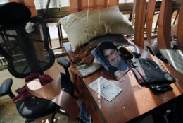 A poster of Hezbollah leader Sayyed Hassan Nasrallah is seen amid other damage inside the media office in a stronghold of the Lebanese Hezbollah group in a southern suburb of Beirut, Lebanon, Sunday, Aug. 25, 2019. Two Israeli drones crashed in a Hezbollah stronghold in the Lebanese capital overnight without the militants firing on them, a spokesman for the group said Sunday, saying the first fell on the roof of a building housing Hezbollah's media office while the second landed in a plot behind it. (AP Photo/Bilal Hussein)