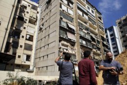 Journalists take pictures of the 11th-floor building that houses Hezbollah's media office as well as nearby buildings suffered minor damage and broken glass in a southern suburb of Beirut, Lebanon, Sunday, Aug. 25, 2019. Two Israeli drones crashed in a Hezbollah stronghold in the Lebanese capital overnight without the militants firing on them, a spokesman for the group said Sunday, saying the first fell on the roof of a building housing Hezbollah's media office while the second landed in a plot behind it. (AP Photo/Bilal Hussein)