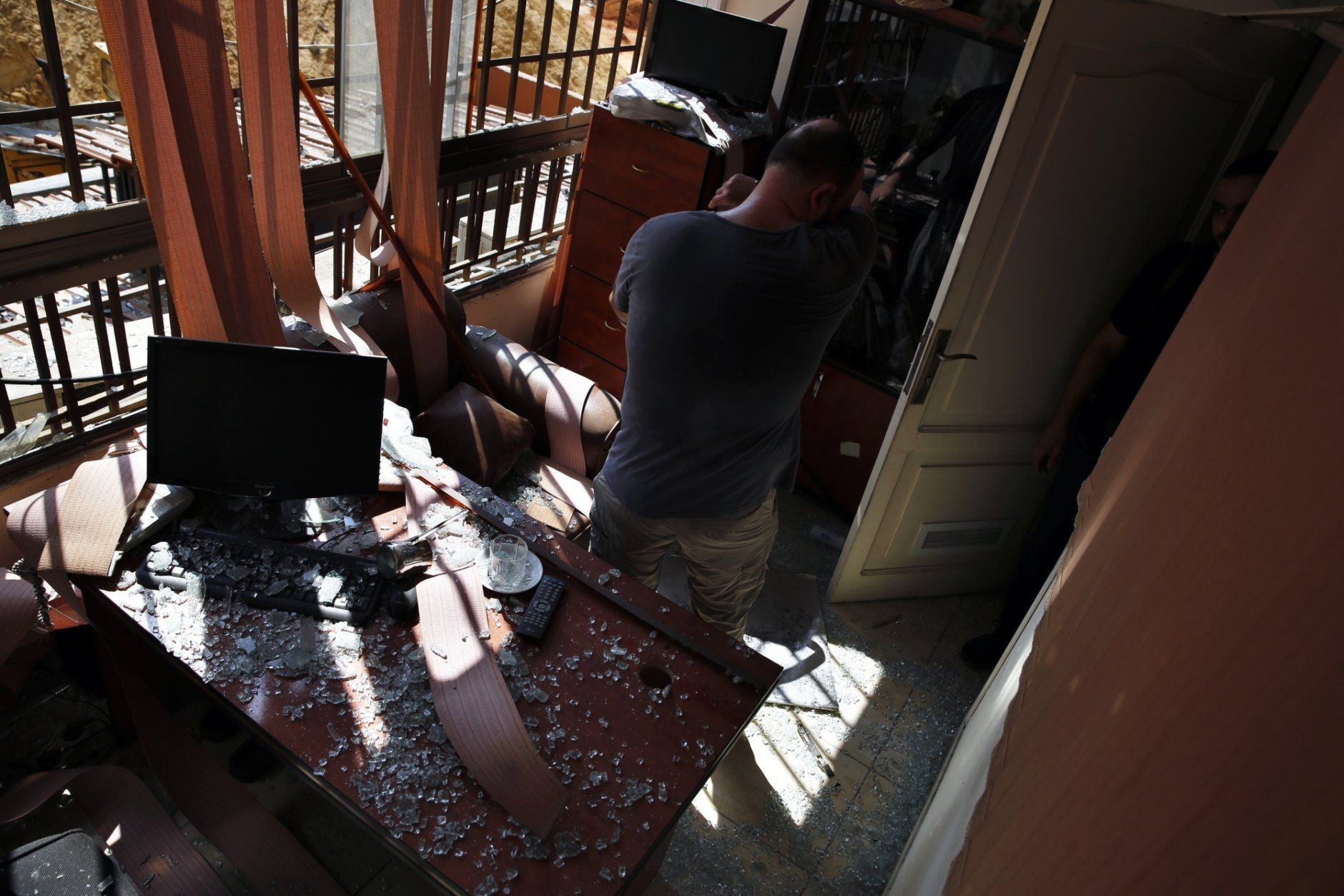 A man stands inside a damaged media office in a stronghold of the Lebanese Hezbollah group, in a southern suburb of Beirut, Lebanon, Sunday, Aug. 25, 2019. Two Israeli drones crashed in a Hezbollah stronghold in the Lebanese capital overnight without the militants firing on them, a spokesman for the group said Sunday, saying the first fell on the roof of a building housing Hezbollah's media office while the second landed in a plot behind it. (AP Photo/Bilal Hussein)