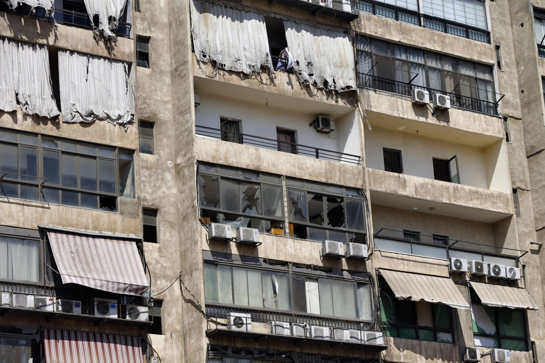 A woman hangs laundry at the 11th-floor building that houses the media office in a stronghold of the Lebanese Hezbollah group, in a southern suburb of Beirut, Lebanon, Sunday, Aug. 25, 2019. Two Israeli drones crashed in a Hezbollah stronghold in the Lebanese capital overnight without the militants firing on them, a spokesman for the group said Sunday, saying the first fell on the roof of a building housing Hezbollah's media office while the second landed in a plot behind it. (AP Photo/Bilal Hussein)