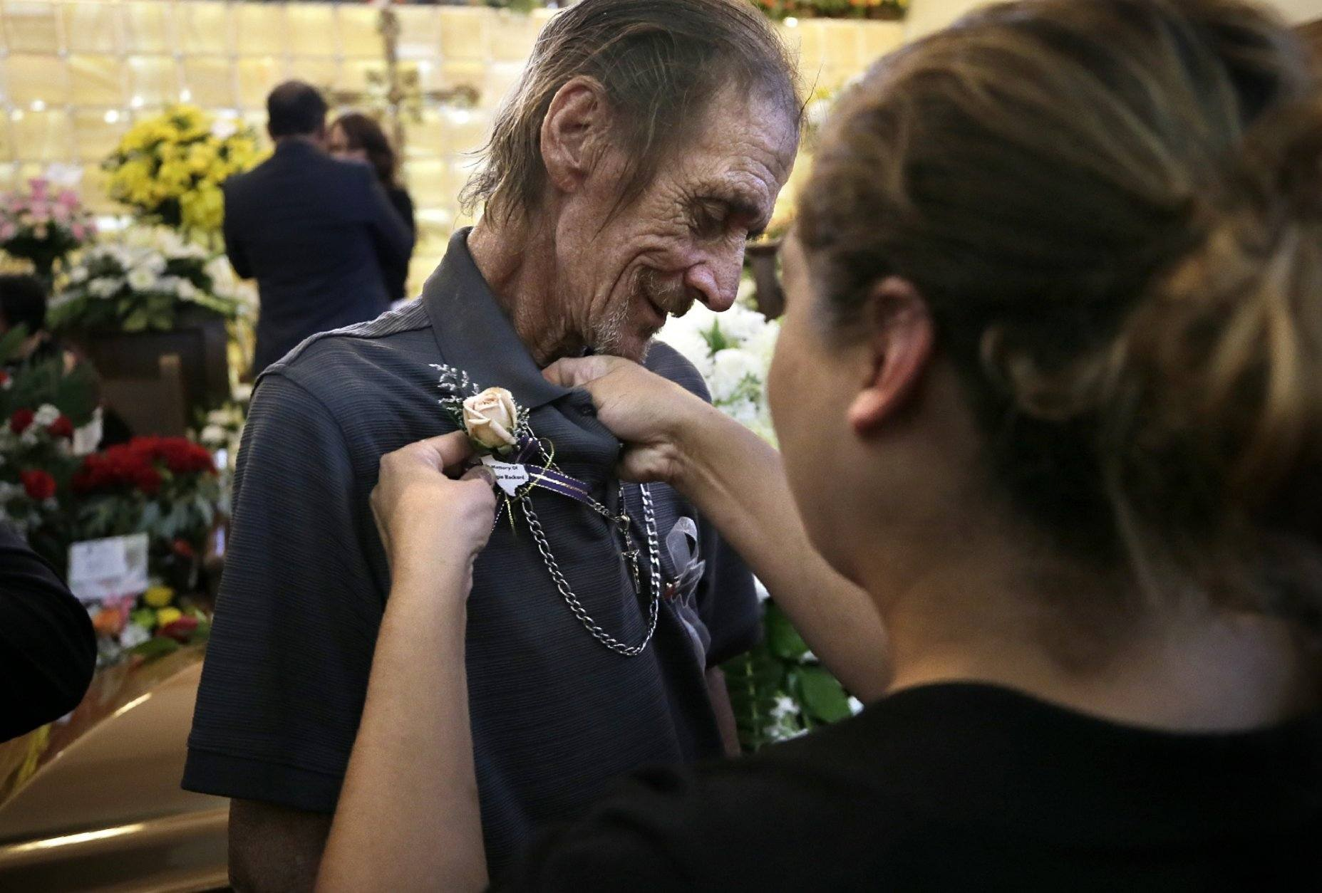 Antonio Basco has a flower pinned to his shirt at the funeral of his companion of 22 years, Margie Reckard, at La Paz Faith Memorial & Spiritual Center, Friday, Aug. 16, 2019, in El Paso, Texas. Reckard was killed during the mass shooting on Aug. 3. (Mark Lambie/The El Paso Times via AP)