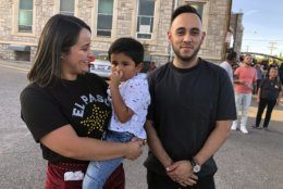 Tania Arzola, 26, left, her son, Derek Flores, 4, and her friend, Martin Olivas, 30, right, stand in line with thousands of others on Friday, Aug. 16, 2019, to pay respects to Margie Reckard, 63, who was killed by a gunman who opened fire at a Walmart in El Paso, Tex., earlier this month. Thousand of strangers from El Paso and around the country came this weekend to honor Reckard. Her long-time companion, Antonio Basco, says he felt so alone planning her funeral, that he invited the world to join him in remembering his companion of 22 years. (AP Photo/Russell Contreras)