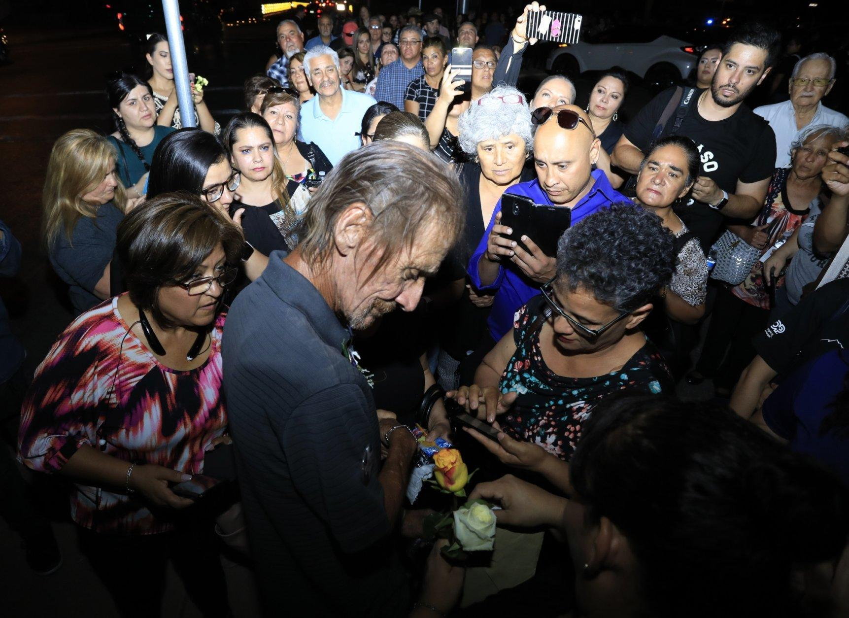 Antonio Bosco, husband of Margie Reckard who lost her life during a shooting, is offered condolences with flowers Friday, Aug. 16, 2019, in El Paso, Texas. Reckard was killed during the mass shooting on Aug. 3. (AP Photo/Jorge Salgado)