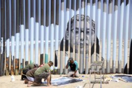 Volunteers help install a new mural on the Mexican side of a border wall that shows faces of people deported from the U.S. with barcodes that activate first-person narratives on visitors' phones, in Tijuana, Mexico, Friday, Aug. 9, 2019. Lizbeth De La Cruz Santana conceived the interactive mural Her project blends Mexico's rich history of muralists with what can loosely be called interactive or performance art on the U.S.-Mexico border. (AP Photo/Joebeth Terriquez)