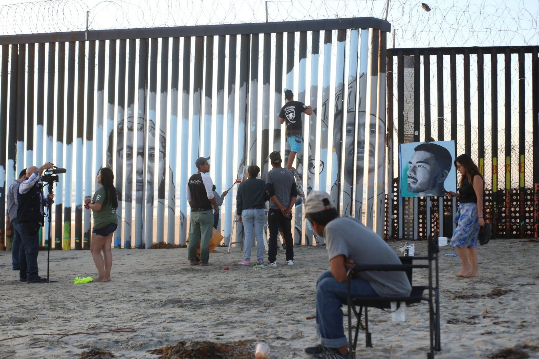 Artist Lizbeth De La Cruz Santana is videotaped during an interview, left, as volunteers help install her new mural on the Mexican side of a border wall that shows faces of people deported from the U.S. with barcodes that activate first-person narratives on visitors' phones, in Tijuana, Mexico, Friday, Aug. 9, 2019. De La Cruz Santana, 28, conceived the interactive mural as part of doctoral dissertation at University of California, Davis, in Spanish with a focus on literature and immigrant experiences.(AP Photo/Joebeth Terriquez)