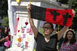 Monica Ortega rises a knitting with black crosses during a tribute for murdered women, in the Alameda park of Mexico City, Saturday, Aug. 24, 2019. A small group of women constructed a memorial made of hand-knit hearts. The knit-in on came on the heels of rowdy protests sparked by outrage over bungled investigations into alleged rapes of teenagers by local policemen. (AP Photo/Ginnette Riquelme)