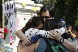 Women hug during a tribute for murdered women, in the Alameda park of Mexico City, Saturday, Aug. 24, 2019. A small group of women constructed a memorial made of hand-knit hearts. The knit-in on came on the heels of rowdy protests sparked by outrage over bungled investigations into alleged rapes of teenagers by local policemen. (AP Photo/Ginnette Riquelme)