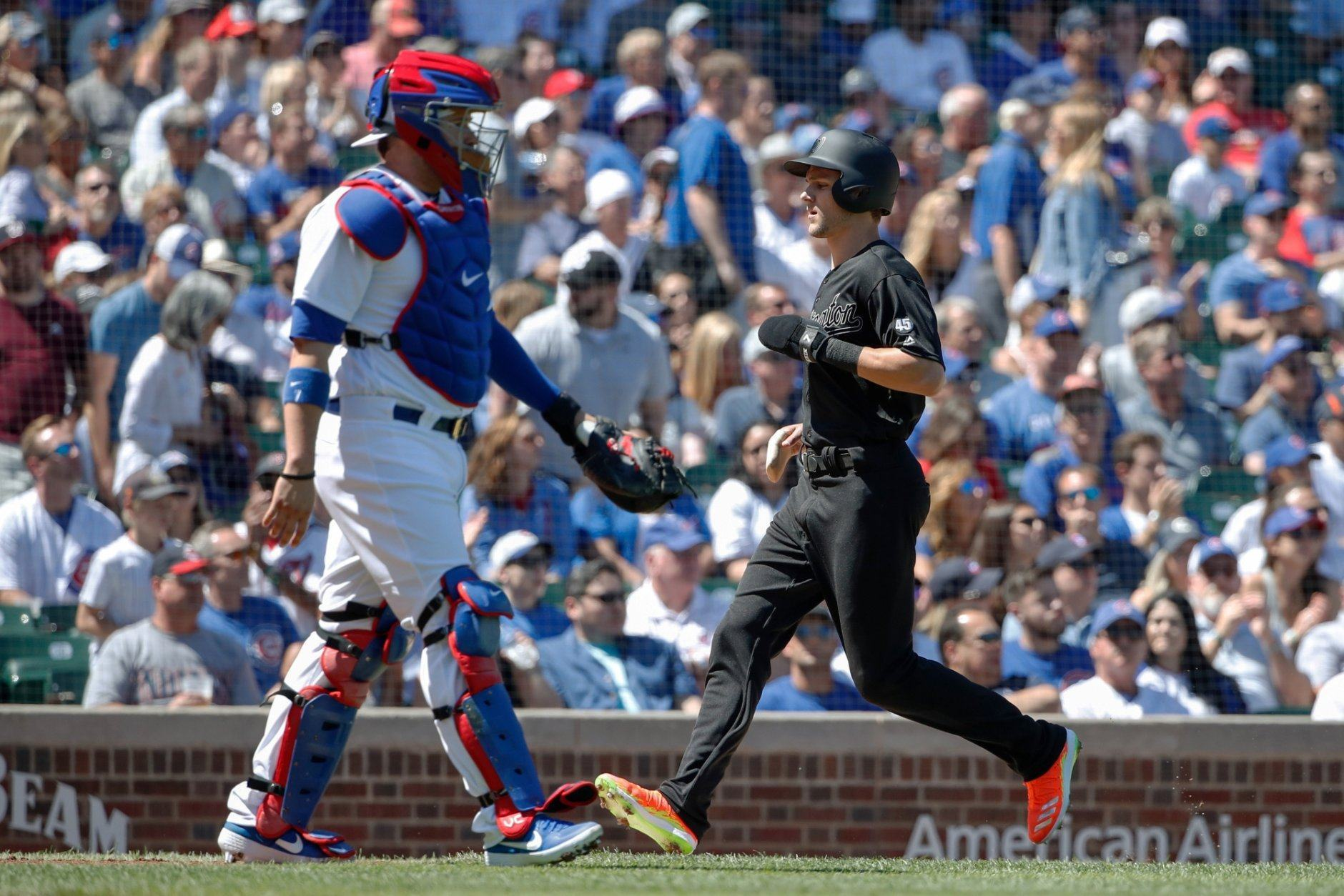 Washington Nationals' Trea Turner, right, scores against the Chicago Cubs on a sacrifice fly hit by Washington Nationals' Anthony Rendon during the first inning of a baseball game, Saturday, Aug. 24, 2019, in Chicago. (AP Photo/Kamil Krzaczynski)