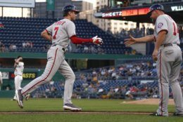 Washington Nationals' Trea Turner (7) is greeted by third base coach Bob Henley after hitting a three-run home run off Pittsburgh Pirates starting pitcher Trevor Williams, back left, in the second inning of a baseball game Monday, Aug. 19, 2019, in Pittsburgh. (AP Photo/Keith Srakocic)