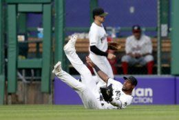 Pittsburgh Pirates center fielder Starling Marte slides along the grass in front of left fielder Bryan Reynolds after catching a fly ball by Washington Nationals' Kurt Suzuki in the first inning of a baseball game Thursday, Aug. 22, 2019, in Pittsburgh. (AP Photo/Keith Srakocic)