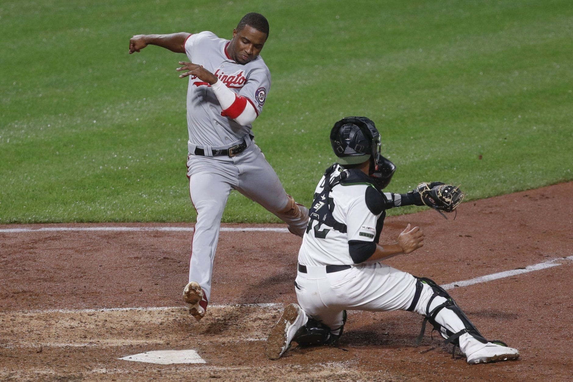 Washington Nationals' Victor Robles, left, twists to avoid a tag by Pittsburgh Pirates catcher Elias Diaz to score on a single by Asdrubal Cabrera in the eighth inning of a baseball game, Thursday, Aug. 22, 2019, in Pittsburgh. (AP Photo/Keith Srakocic)