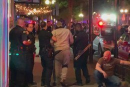 In this image made from video provided by Jeff Oaks, first responders help walk an injured person after a deadly shooting in Dayton, Ohio, Sunday, Aug. 4, 2019. A gunman in body armor opened fire early Sunday in a popular entertainment district in Dayton, Ohio, killing several people, including his sister, and wounding dozens of others before he was quickly slain by police, city officials said. (Jeff Oaks via AP)