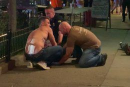 In this image made from video provided by Jeff Oaks, emergency workers and an unidentified person, left, tend to an injured person on the sidewalk after a deadly shooting in Dayton, Ohio, Sunday, Aug. 4, 2019. A gunman in body armor opened fire early Sunday in a popular entertainment district in Dayton, Ohio, killing several people, including his sister, and wounding dozens of others before he was quickly slain by police, city officials said. (Jeff Oaks via AP)