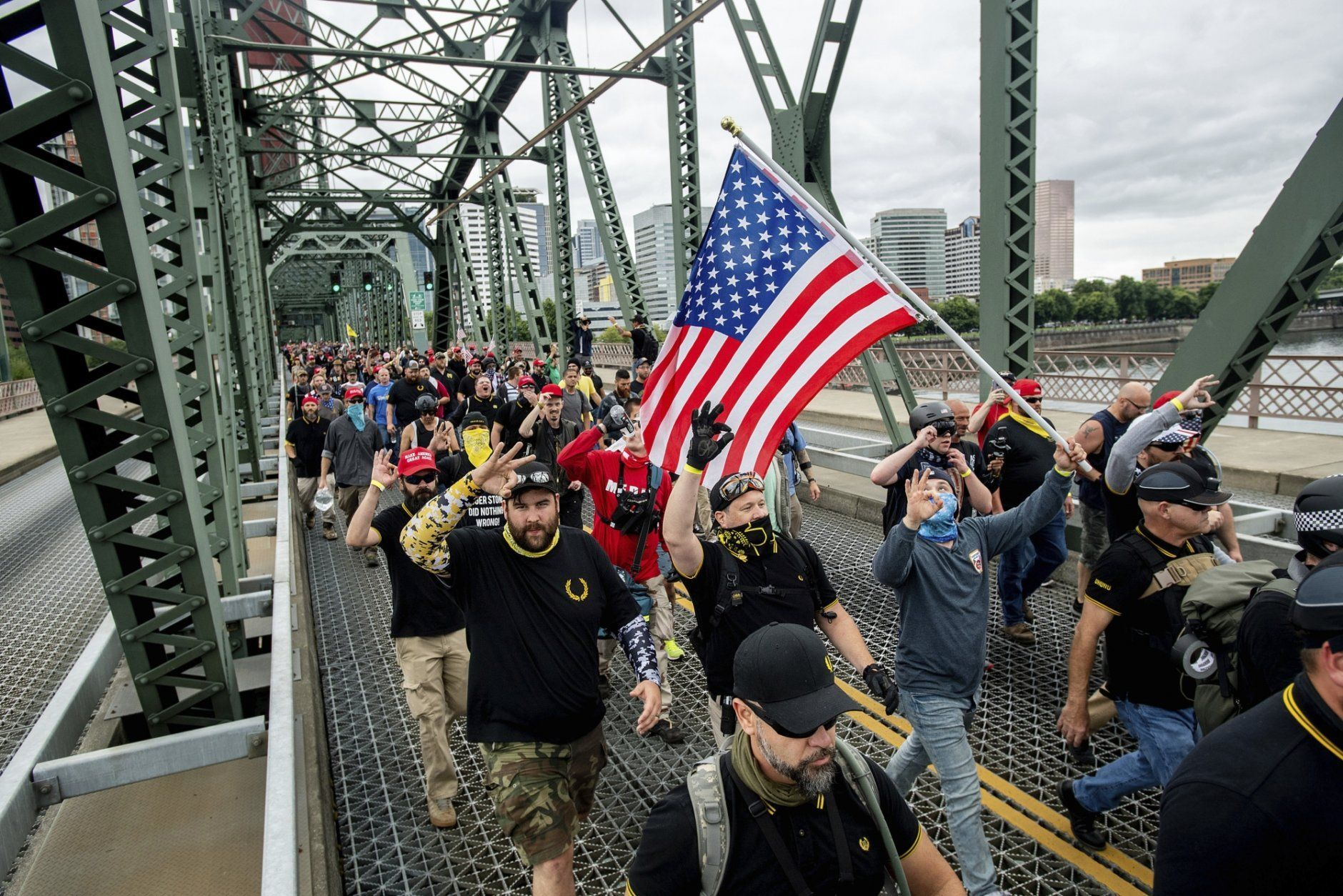 "Members of the Proud Boys and other right-wing demonstrators march across the Hawthorne Bridge during an ""End Domestic Terrorism"" rally in Portland, Ore., on Saturday, Aug. 17, 2019. Police have mobilized to prevent clashes between conservative groups and counter-protesters who converged on the city. (AP Photo/Noah Berger)"
