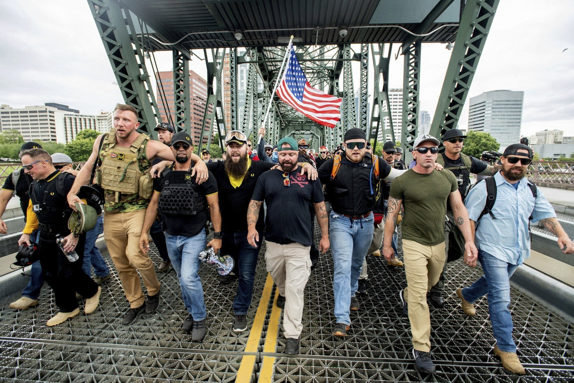 "Members of the Proud Boys and other right-wing demonstrators march across the Hawthorne Bridge during an ""End Domestic Terrorism"" rally in Portland, Ore., on Saturday, Aug. 17, 2019. The group includes organizer Joe Biggs, center in green hat, and Proud Boys Chairman Enrique Tarrio, holding megaphone. (AP Photo/Noah Berger)"