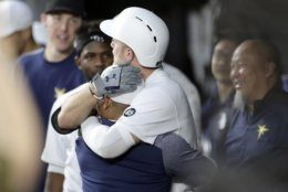 Tampa Bay Rays' Austin Meadows, center right, hugs a teammate after hitting a grand slam off Baltimore Orioles starting pitcher Ty Blach during the second inning of a baseball game, Friday, Aug. 23, 2019, in Baltimore. Rays' Mike Zunino, Matt Duffy and Tommy Pham also scored on the grand slam. (AP Photo/Julio Cortez)