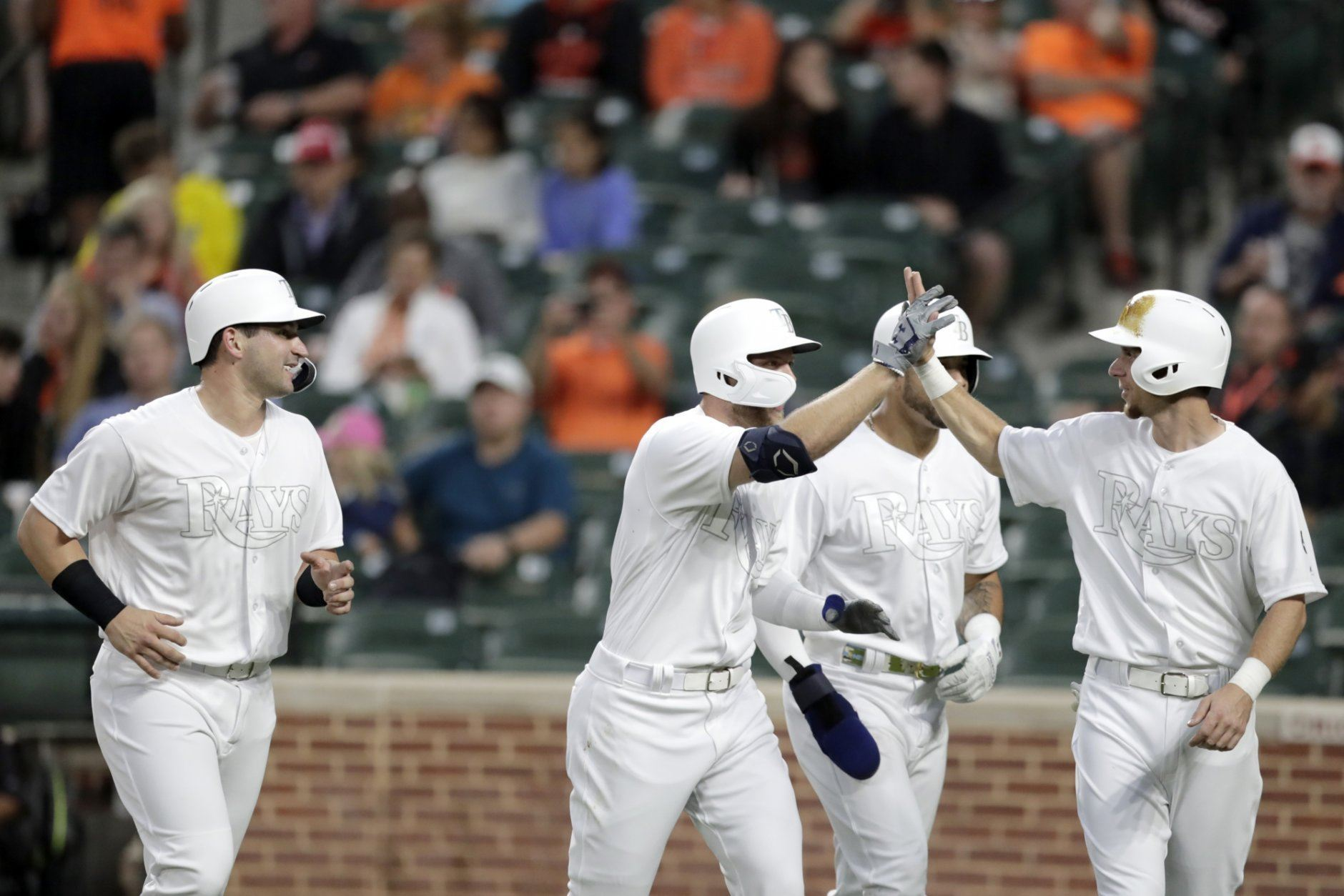 Tampa Bay Rays' Austin Meadows, center left, celebrates with Matt Duffy, right, as Mike Zunino, left, and Tommy Pham, back, look on after Meadows scored them all on a grand slam off Baltimore Orioles starting pitcher Ty Blach during the second inning of a baseball game, Friday, Aug. 23, 2019, in Baltimore. (AP Photo/Julio Cortez)