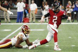 Atlanta Falcons quarterback Matt Ryan (2) escapes a tackle by Washington Redskins linebacker Josh Harvey-Clemons (40) during the first half an NFL preseason football game, Thursday, Aug. 22, 2019, in Atlanta. (AP Photo/John Bazemore)