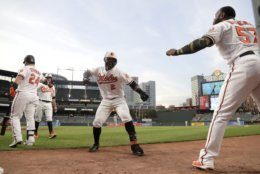 Baltimore Orioles' Jonathan Villar (2) is greeted near the dugout by Hanser Alberto (57) after hitting a two run home run off Kansas City Royals starting pitcher Mike Montgomery during the second inning of a baseball game, Wednesday, Aug. 21, 2019, in Baltimore. (AP Photo/Julio Cortez)