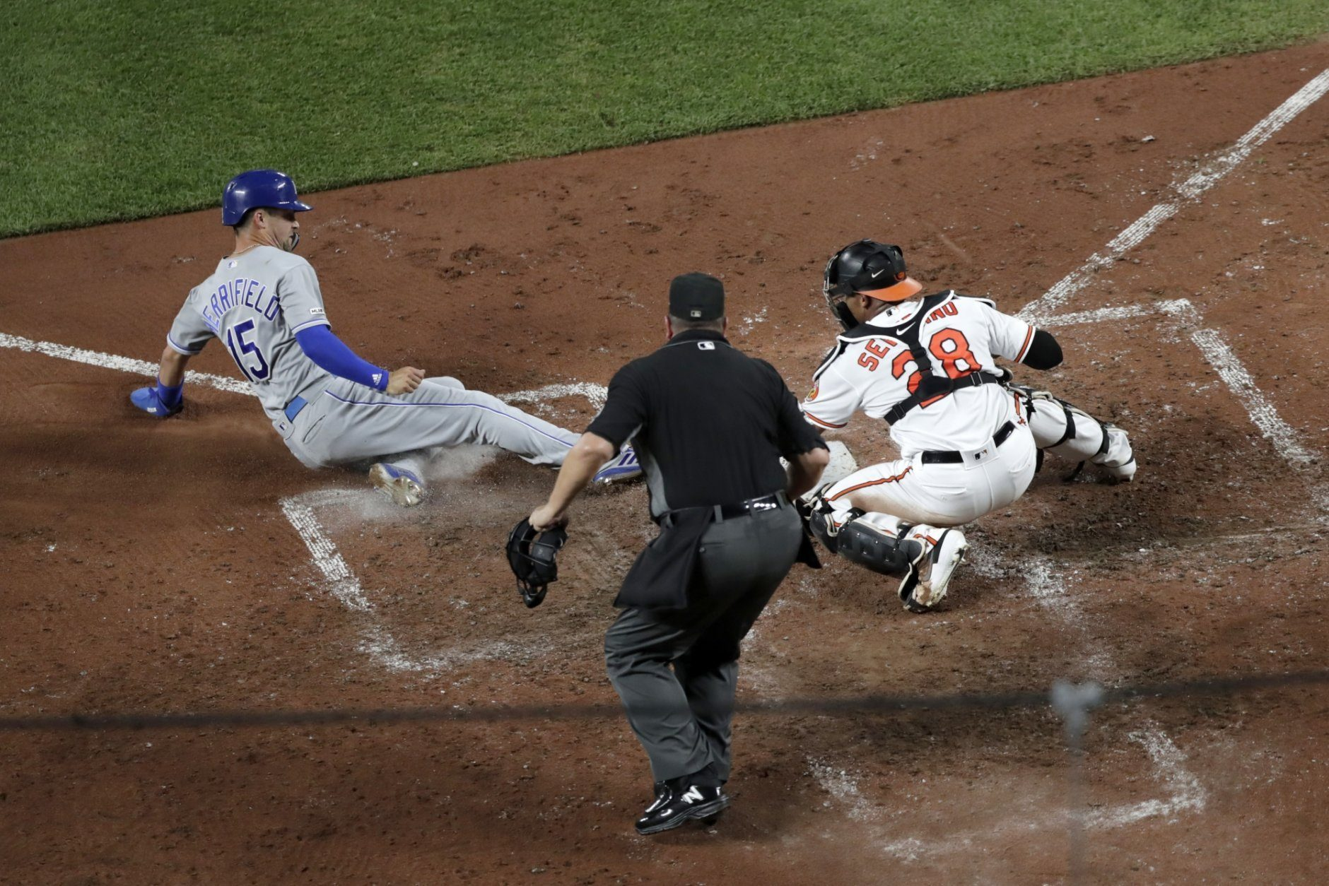 Kansas City Royals' Whit Merrifield (15) scores under the tag of Baltimore Orioles catcher Pedro Severino (28) as home plate umpire Sam Holbrook looks on during the sixth inning of a baseball game, Monday, Aug. 19, 2019, in Baltimore. (AP Photo/Julio Cortez)