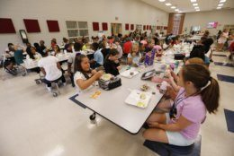 Students at Madison Crossing Elementary School in Canton, Miss., eat lunch in the school's cafeteria on Friday, Aug. 9, 2019. Scott Clements, director of child nutrition at the Mississippi education department, said they've ordered two truckloads of trade mitigation pulled pork and four loads of kidney beans for use in their school meal plans. The products are coming from the U.S. Department of Agriculture, which is giving away the foods it's buying to help farmers hurt by trade negotiations. (AP Photo/Rogelio V. Solis)