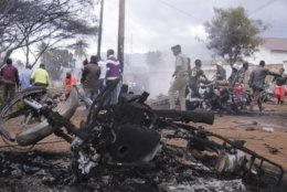EDS NOTE GRAPHIC CONTENT - Destroyed motorbikes and debris litter the scene as a victim is carried away after a patrol tanker exploded, Saturday, Aug. 10 2019, in Morogoro, Tanzania.  A damaged tanker truck exploded in eastern Tanzania Saturday as people were trying to siphon fuel out of it, killing at least 62, in one of the worst incidents of its kind in the East African country. (AP Photo)