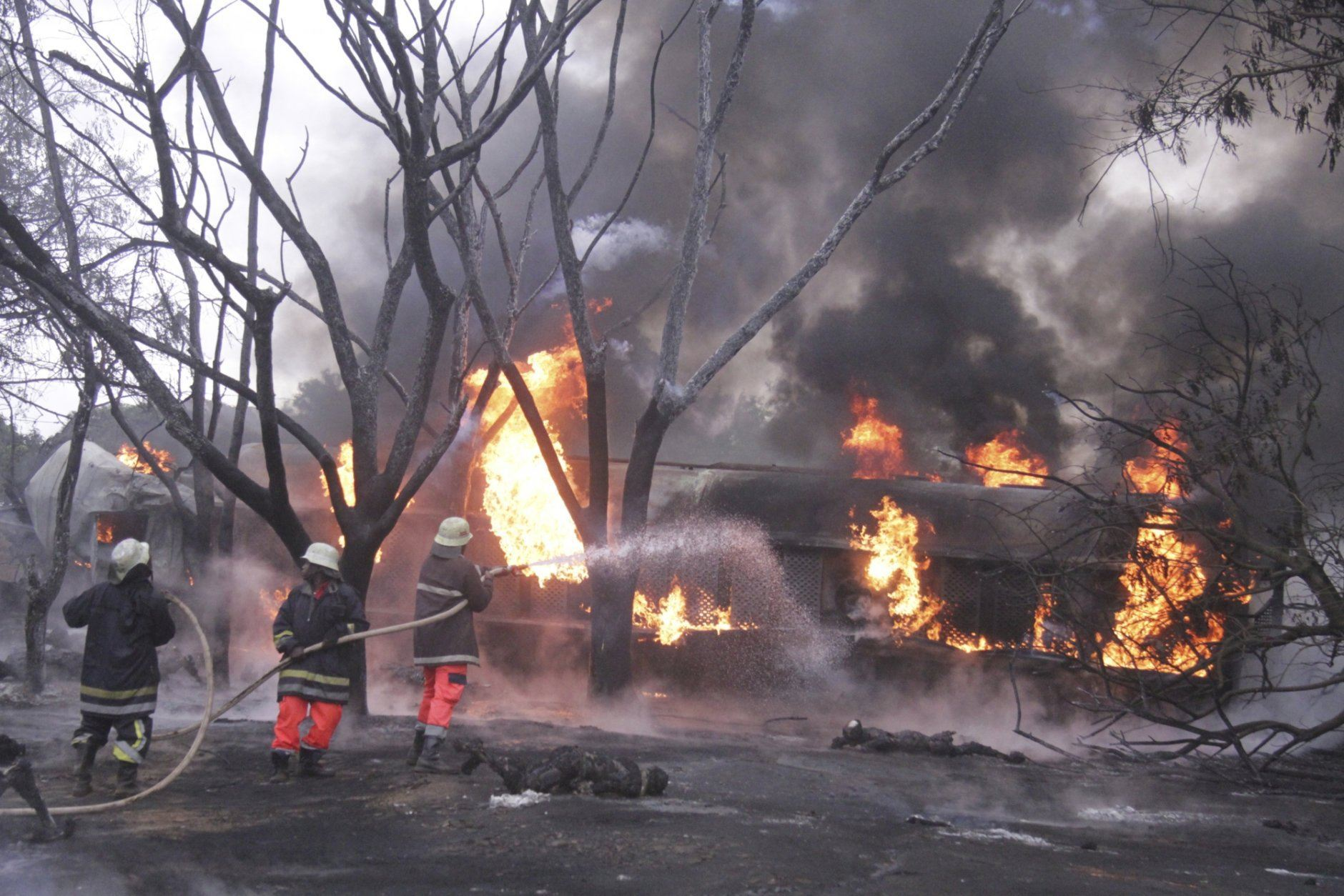 Fire fighters try to extinguish a Patrol Tanker blaze, Saturday, Aug. 10 2019, in Morogoro, Tanzania.   A damaged tanker truck exploded in eastern Tanzania Saturday as people were trying to siphon fuel out of it, killing at least 62, in one of the worst incidents of its kind in the East African country. (AP Photo)