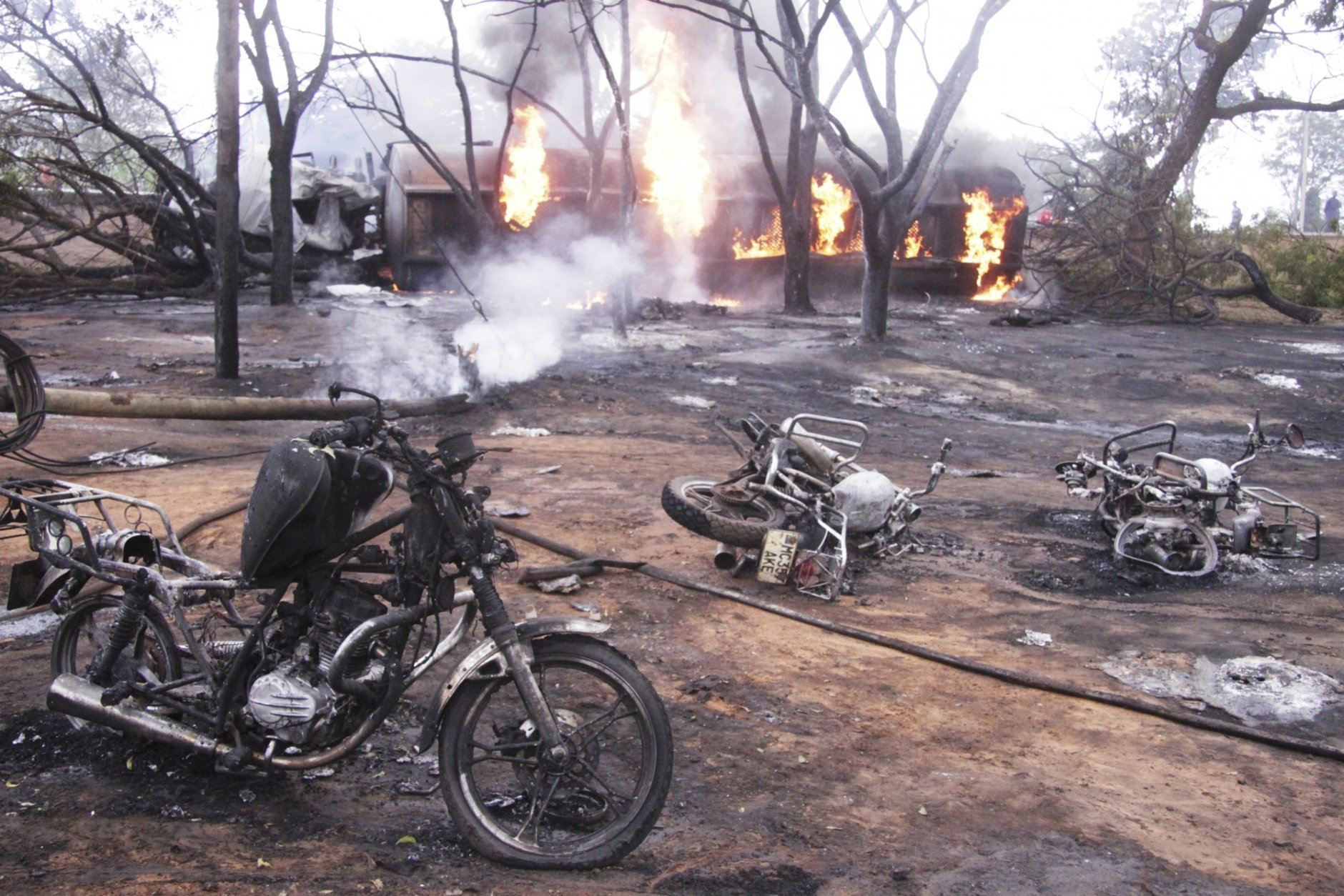 Destroyed motorbikes and debris litter the scene as a patrol tanker burns in the background, Saturday, Aug. 10 2019, in Morogoro, Tanzania.  A damaged tanker truck exploded in eastern Tanzania Saturday as people were trying to siphon fuel out of it, killing at least 62, in one of the worst incidents of its kind in the East African country. (AP Photo)