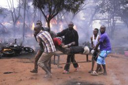 An injured man is carried from the scene as a patrol tanker burns in the background, Saturday, Aug. 10 2019, in Morogoro, Tanzania.  A damaged tanker truck exploded in eastern Tanzania Saturday as people were trying to siphon fuel out of it, killing at least 62, in one of the worst incidents of its kind in the East African country. (AP Photo)