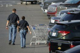 Police officers walk by shopping carts at the scene of a mass shooting at a shopping complex Sunday, Aug. 4, 2019, in El Paso, Texas. (AP Photo/John Locher)