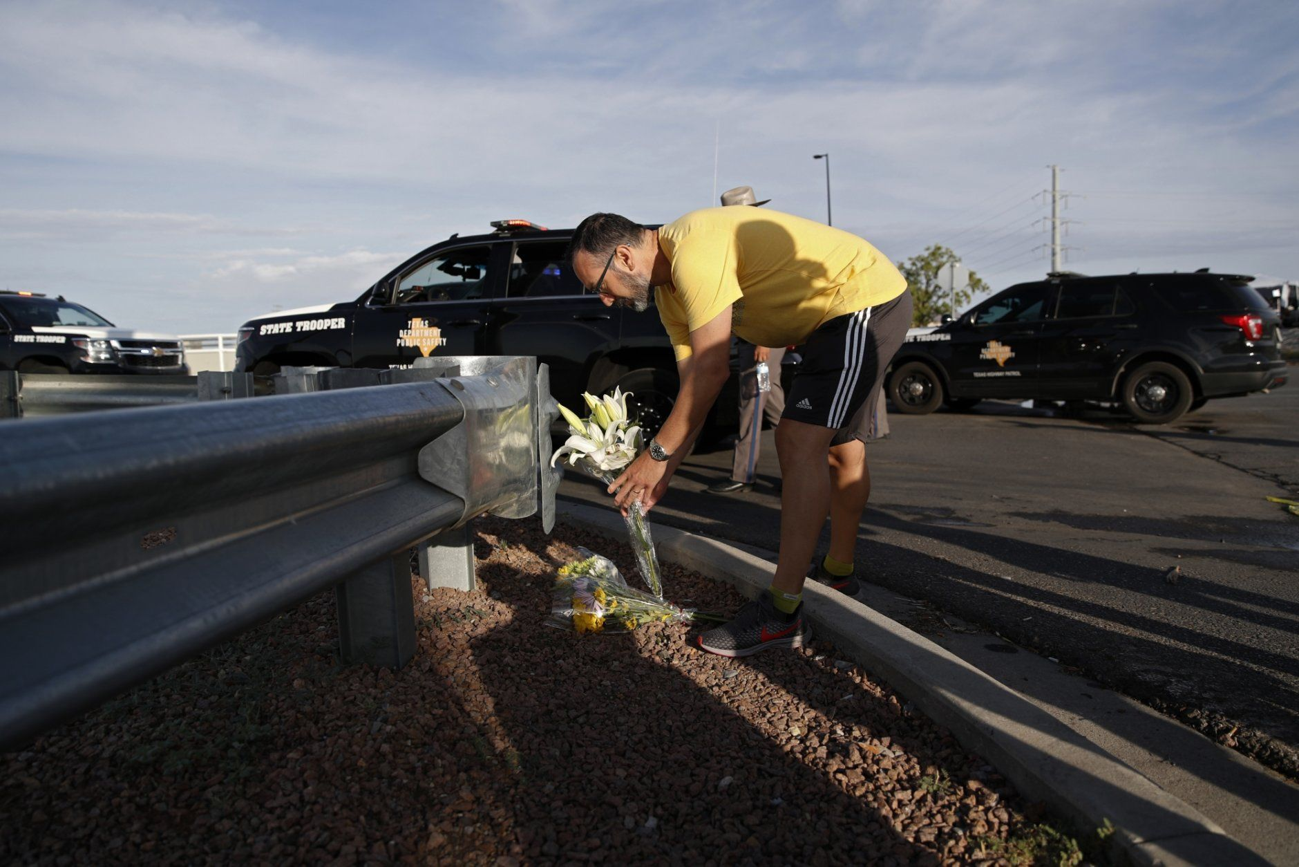 A man leaves flowers near the scene of a mass shooting at a shopping complex Sunday, Aug. 4, 2019, in El Paso, Texas. (AP Photo/John Locher)