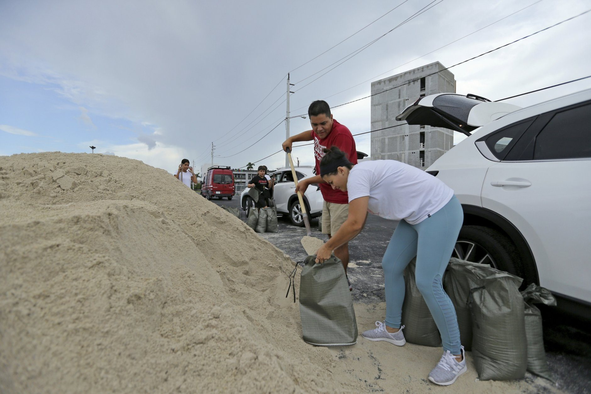 Farah y Max Cicardini fill sandbags at the parking of the Big Easy Casino, Friday, Aug. 30, 2019 in Hallandale Beach, Fla.  Hurricane Dorian was muscling a chaotic path toward Florida, with officials and residents bracing for the possibility it would unleash its full fury early next week but clinging to the glimmer of hope that the strengthening storm could simply skirt the coastline. (David Santiago/Miami Herald via AP)