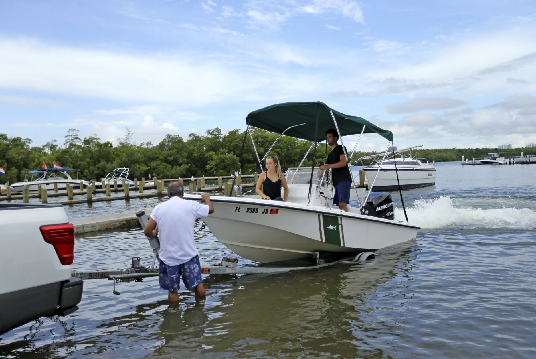 Renan Fuentes, left, Kevin Fuentes, right, and his girlfriend Alexia Mikhalides pull out his boat from the Haulover Marine Center, Friday, Aug. 30, 2019 in Miami Beach, Fla. Hurricane Dorian was muscling a chaotic path toward Florida, with officials and residents bracing for the possibility it would unleash its full fury early next week but clinging to the glimmer of hope that the strengthening storm could simply skirt the coastline. (David Santiago/Miami Herald via AP)