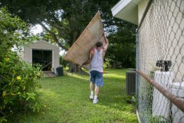 Colin Johnson carries plywood as he prepares to board a window at his father's home in preparation for Hurricane Dorian, Friday, Aug. 30, 2019, in Vero Beach, Fla. Johnson's father, Larry, unexpectedly died Thursday. (Matias J. Ocner/Miami Herald via AP)