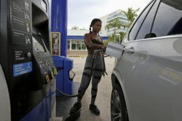 Suni Sweeney fills up her car at a Marathon gas station on Biscayne Boulevard, Friday, Aug. 30, 2019, in Aventura, Fla., as residents prepare for Hurricane Dorian. (David Santiago/Miami Herald via AP)