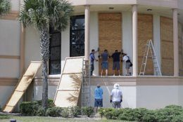 Workers cover stained glass windows with plywood sections at the Santa Maria del Mar Catholic Church in preparation for Hurricane Dorian, Friday, Aug. 30, 2019, in Flagler Beach, Fla. (AP Photo/John Raoux)