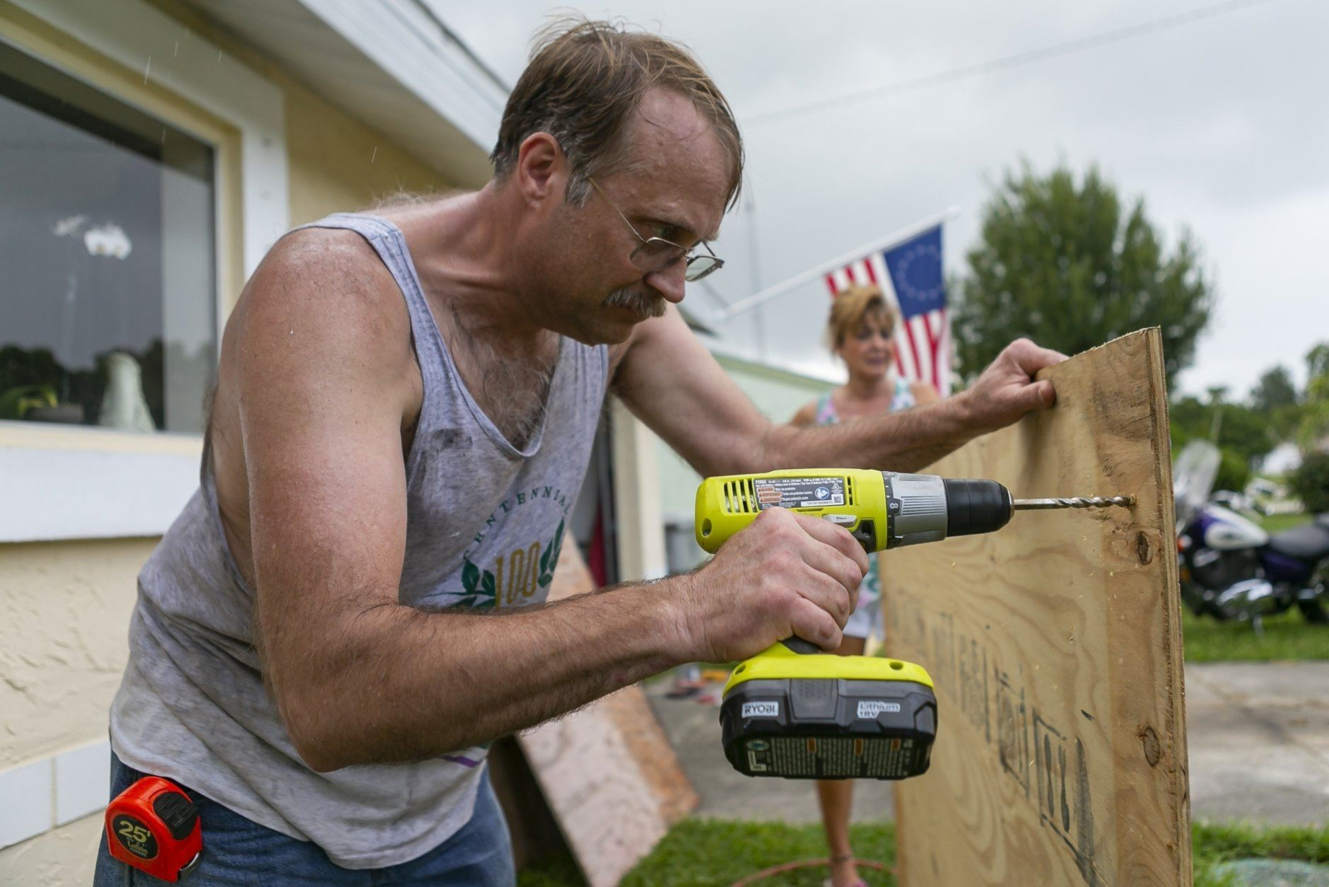 Colin Johnson drills plywood as he prepares to board a window at his father's home in preparation for Hurricane Dorian, Friday, Aug. 30, 2019, in Vero Beach, Fla. Johnson's father, Larry, unexpectedly died Thursday. (Matias J. Ocner/Miami Herald via AP)
