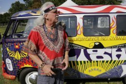 """FILE - In this Thursday, Aug. 15, 2019 file photo, a man who calls himself """"Run-A-Way Bill"""" stands in front of a Volkswagen bus while waiting for the gates to open at a Woodstock 50th anniversary event in Bethel, N.Y.  Fifty years at Woodstock, the mystical and messy event that became the father of all musical festivals, the entertainment industry is diluted with festivals and events like it, some genre specific, some extremely diverse and others offering experiences in addition to music, ranging from food to art, in order to appeal to wider audiences. (AP Photo/Seth Wenig)"""