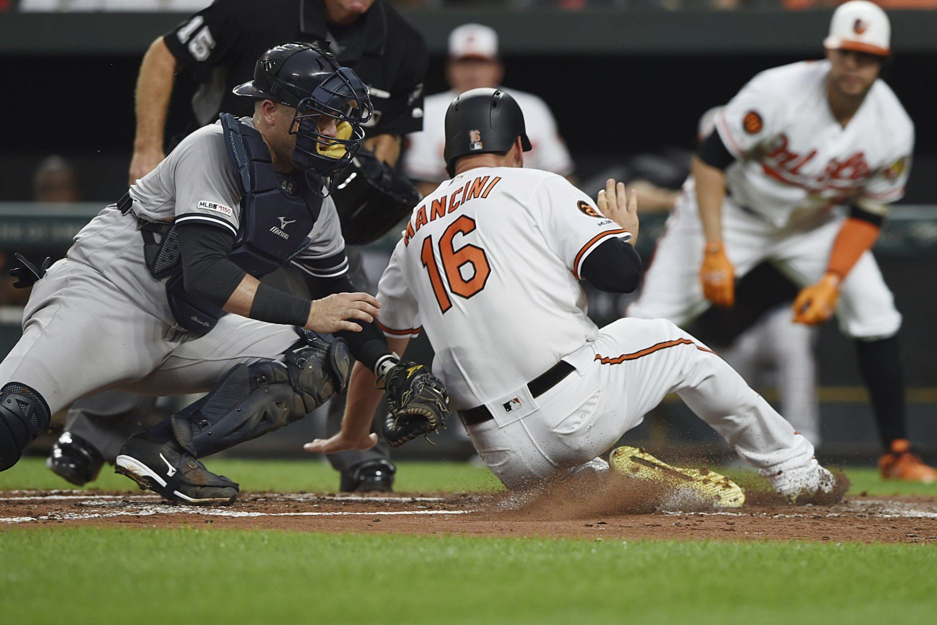 Baltimore Orioles' Trey Mancini (16) is tagged out by New York Yankees catcher Austin Romine, left, in the third inning of a baseball game, Monday, Aug. 5, 2019, in Baltimore. (AP Photo/Gail Burton)