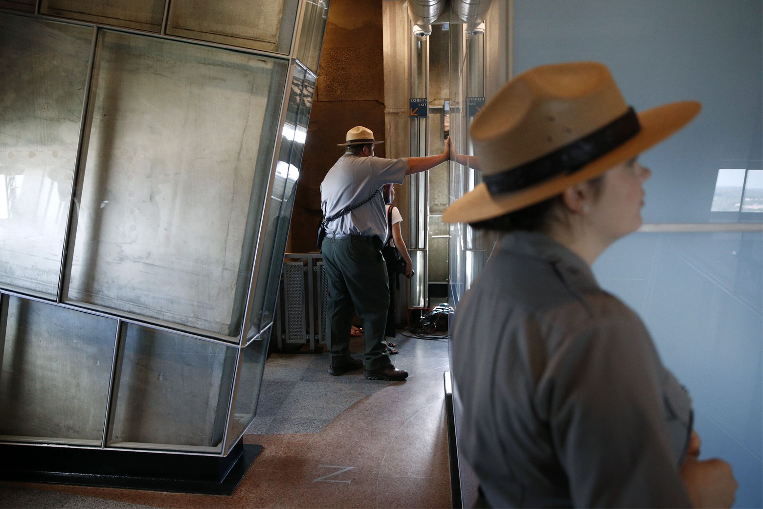 National Parks Service park rangers gather near glass panels that provide a view of interior sections of the Washington Monument's observation level during a press preview tour ahead of the monument's official reopening, Wednesday, Sept. 18, 2019, in Washington. The monument, which has been closed to the public since August 2016, is scheduled to re-open Thursday, Sept. 19. (AP Photo/Patrick Semansky)