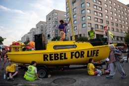 Protesters with Extinction Rebellion use a sailboat to block the intersection of K and 16th streets in downtown Washington, D.C. on Sept. 23, 2019. Environmental activists pressured lawmakers to declare a climate change emergency by paralyzing morning traffic in the nation's capital. (WTOP/Alejandro Alvarez)