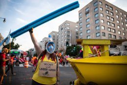 A protester with Extinction Rebellion wears a snorkel near a sailboat blocking the intersection of K and 16th streets in Washington, D.C. on Sept. 23, 2019. Environmental activists pressured lawmakers to declare a climate change emergency by paralyzing morning traffic in the nation's capital. (WTOP/Alejandro Alvarez)