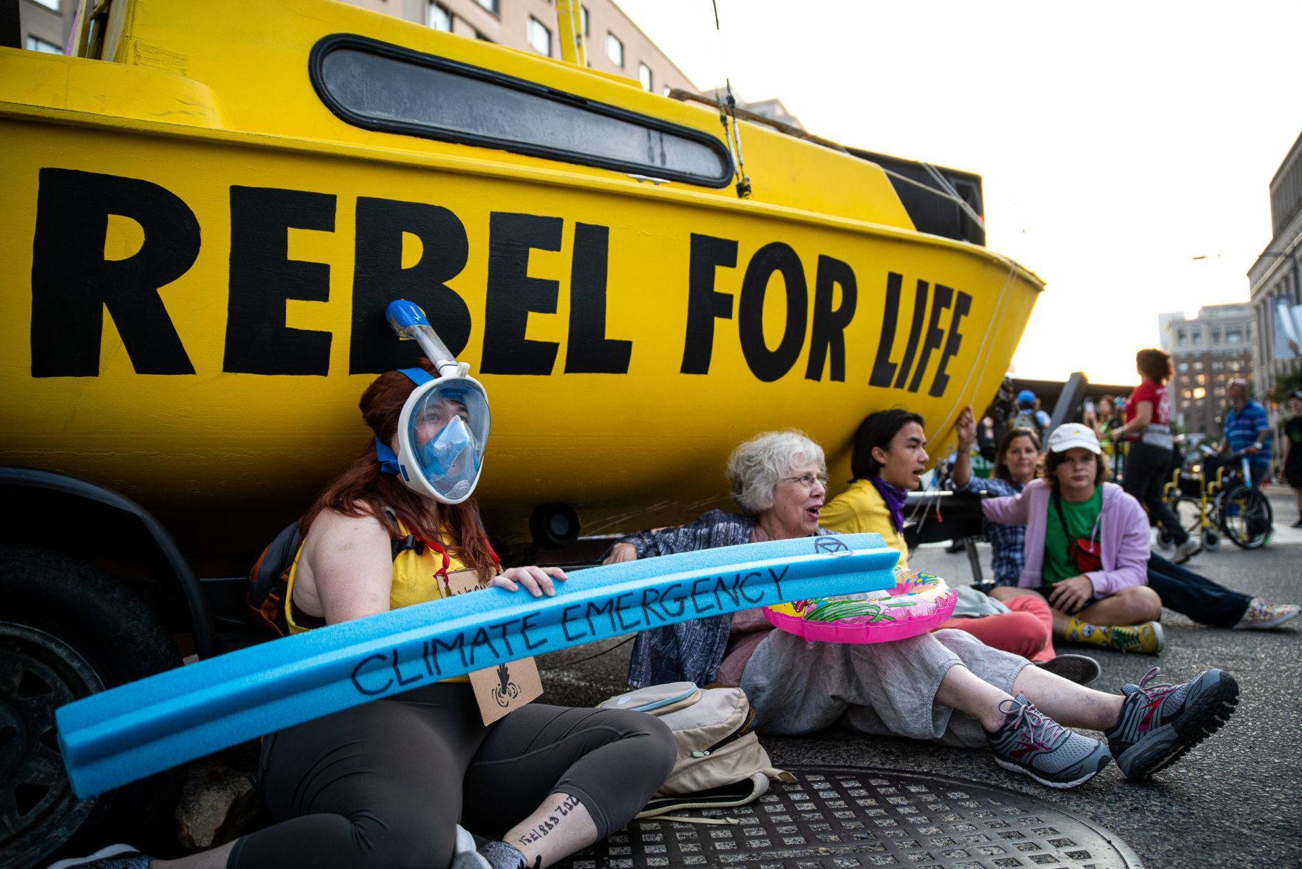Protesters with Extinction Rebellion stage a sit-in beneath their sailboat blockade at the intersection of K and 16th streets in Washington, D.C. on Sept. 23, 2019. Environmental activists pressured lawmakers to declare a climate change emergency by paralyzing morning traffic in the nation's capital. (WTOP/Alejandro Alvarez)