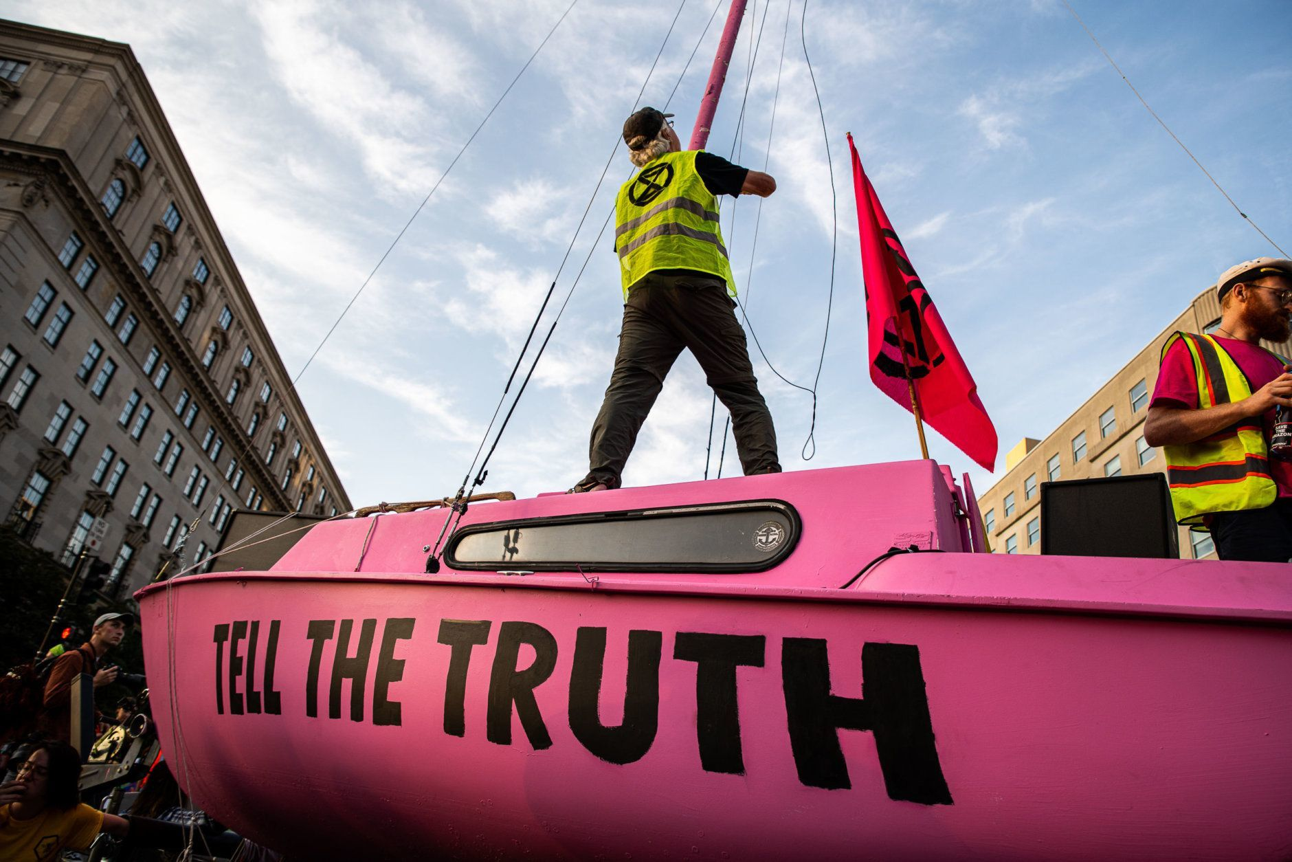 A member of Extinction rebellion hoists the group's hourglass emblem on a sailboat blocking the intersection of K and 16th streets in downtown D.C. on Sept. 23, 2019. Environmental activists pressured lawmakers to declare a climate change emergency by paralyzing morning traffic in the nation's capital. (WTOP/Alejandro Alvarez)