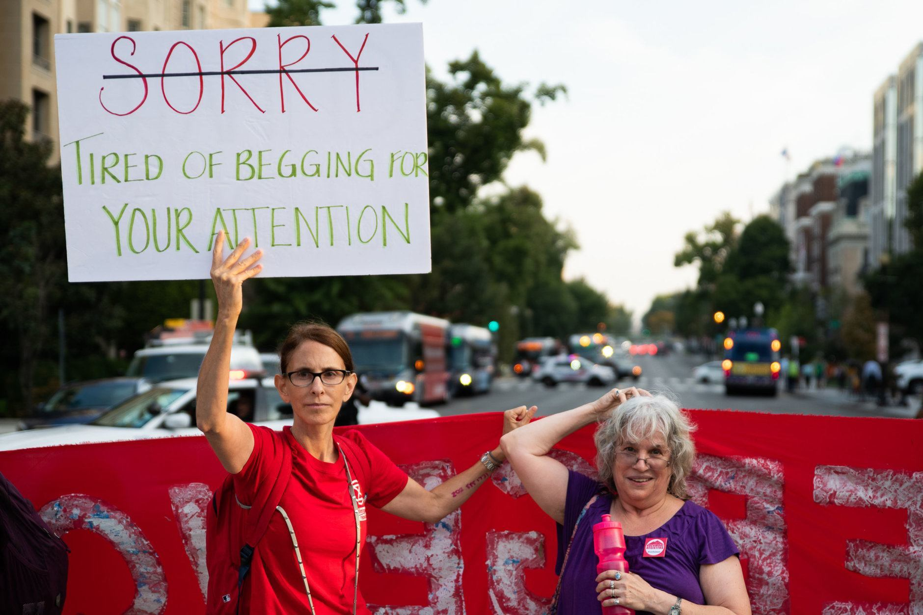 A protester explains justifies her blocking of traffic to commuters impacted by an Extinction Rebellion action in downtown D.C. on Sept. 23, 2019. Environmental activists pressured lawmakers to declare a climate change emergency by paralyzing morning traffic in the nation's capital. (WTOP/Alejandro Alvarez)