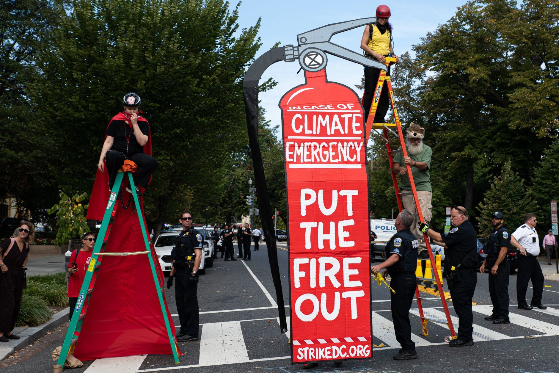 A group of Extinction Rebellion protesters hold the intersection of Massachusetts Avenue and 18th streets near Dupont Circle, chaining themselves to ladders. (WTOP/Alejandro Alvarez)